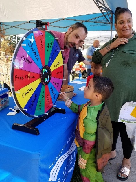 District staff helps kid spin prize wheel after his mom votes for